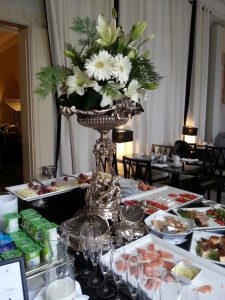 Cold breakfast items laid out around a splendid silver centrepiece.