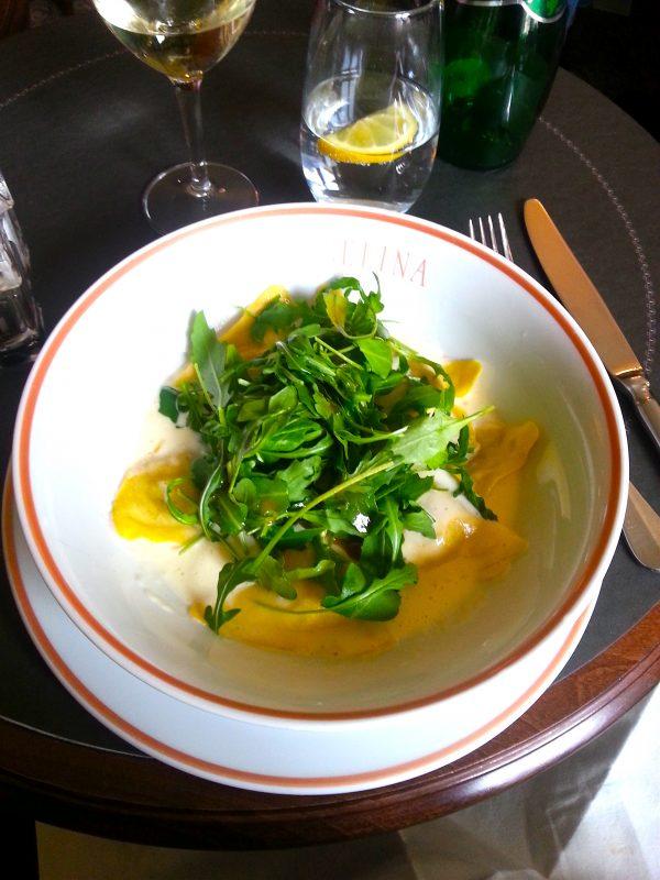 Truffle ravioli with fresh garnished with fresh greens.