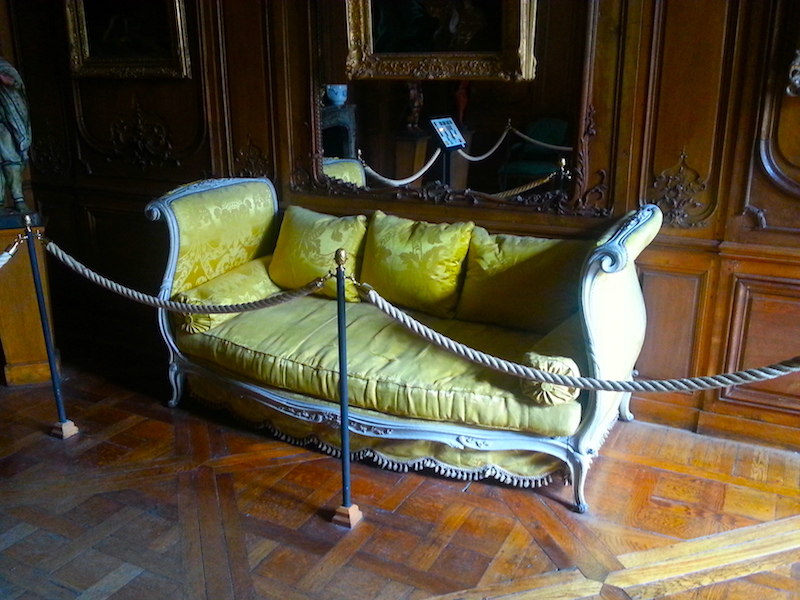 A yellow-upholstered lit de travers, or daybed, in the Carnavalet Museum.
