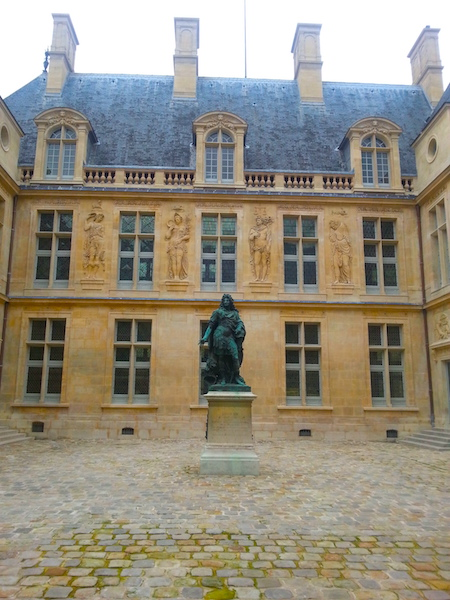 An equestrian statue of Louis XIV presides over a 17C courtyard of the museum.