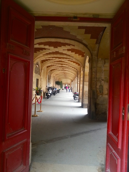 An arcade along one side of the Place des Vosges.